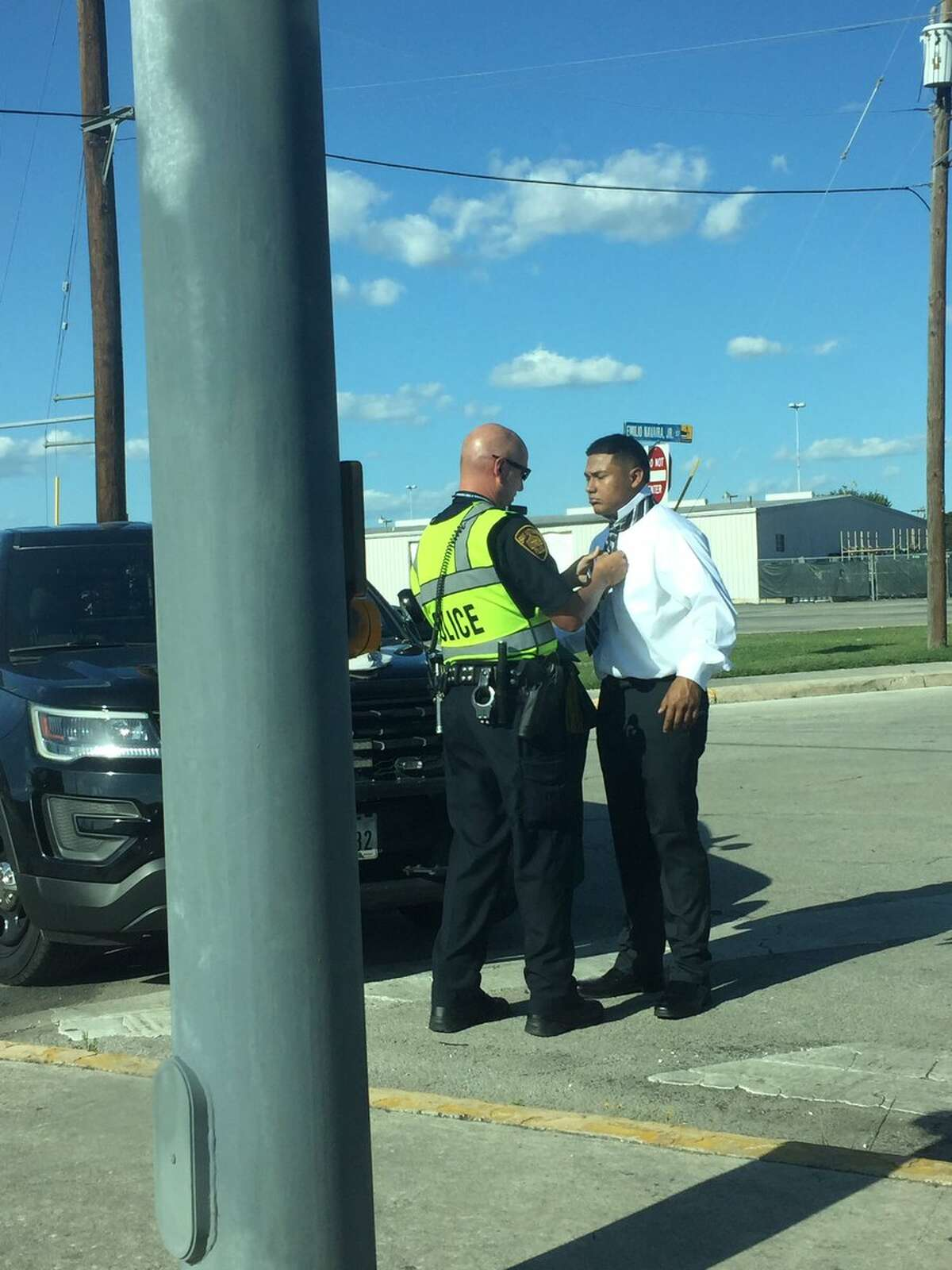 Holmes High School graduate Robert Perez got tie help from an unidentified SAPD officer before his graduation on June 6, 2017.