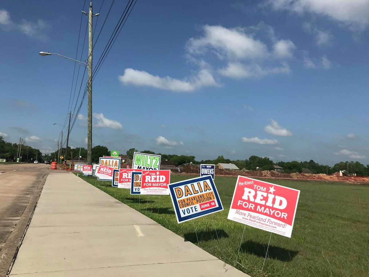 Campaign signs on June 6, 2017 line the roadway leading to an early voting election site during the city of Pearland runoff.