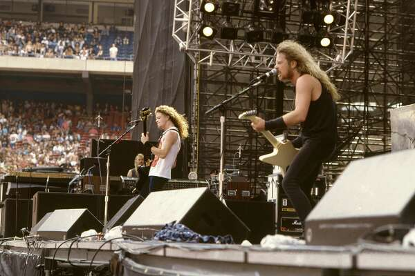 """HOUSTON - JULY 2: Bassist Jason Newsted and Singer and guitarist James Hetfield of the heavy metal quartet """"Metallica"""" perform onstage at the """"Monsters of Rock"""" festival at Rice Stadium on July 2, 1988 in Houston, Texas. (Photo by Michael Ochs Archives/Getty Images)"""