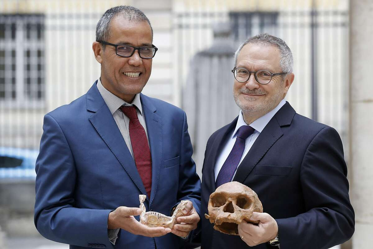 French paleoanthropologist Jean-Jacques Hublin (R) and Abdelouahed Ben-Ncer of the National Institute of Archaeology and Heritage Sciences in Morocco pose with the casting of a skull of Homo Sapiens discovered in Morocco on June 6, 2017 in Paris. Our human species already roamed Africa 300,000 years ago, sporting modern-looking faces that would not stand out in a crowd today, according to research published on June 7, 2017 that advanced Homo sapiens' origins by a hundred millennia. A groundbreaking fossil discovery in Morocco obliterates two decades of scientific consensus that our forefathers emerged in East Africa about 200,000 years ago, according to two studies published in the science journal Nature. / AFP PHOTO / PATRICK KOVARIKPATRICK KOVARIK/AFP/Getty Images