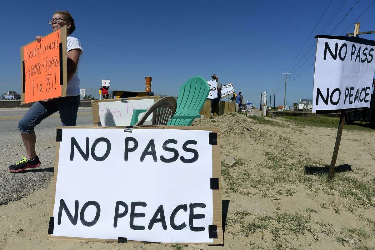 Buffy Dievel, of High Island, holds a protest sign at Rollover Pass on the Bolivar Peninsula on April 24. Galveston County commissioners have approved a settlement agreement for the $1.75 million purchase of Rollover Pass, advancing plans to close one of Texas' most renowned fishing spots following a long legal battle.