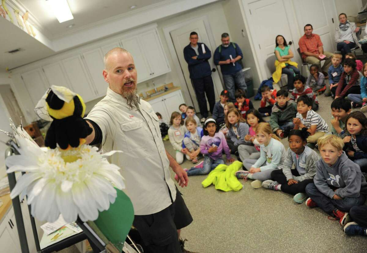 Audubon Greenwich Education Specialist James Flynn demonstrates how bees pollinate flowers to a group of International School at Dundee first-graders on a class trip to Audubon Greenwich in Greenwich, Conn. Wednesday, June 7, 2017.