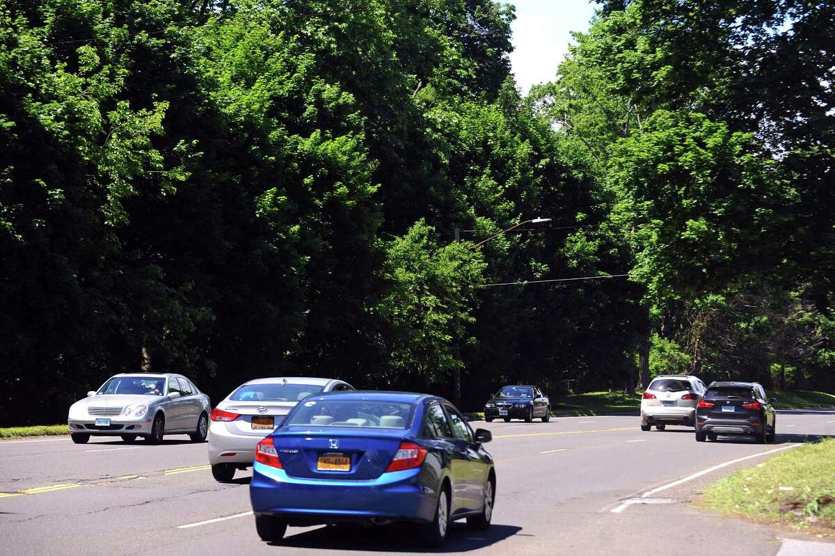 Cars zip past a wooden section of Long Ridge Rd., where BLT wants to build 800 units of housing, in Stamford.