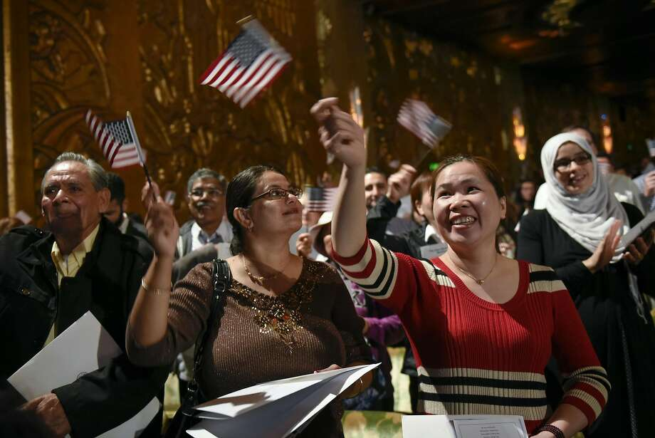 New U.S. citizens wave flags during a citizenship ceremony at Oakland's Paramount Theater. Photo: Michael Short, Special To The Chronicle