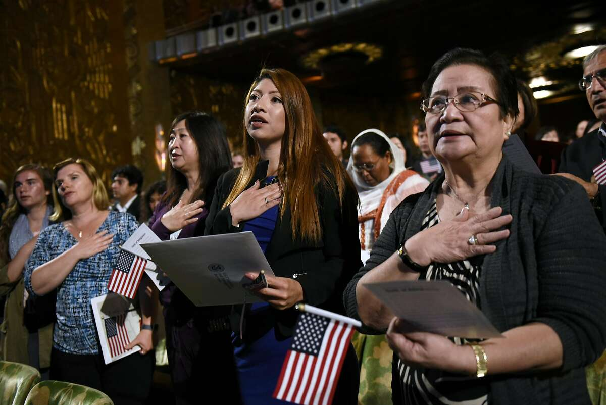 New U.S. citizens Vivian Palacios, center, of Guatemala, and Alicia DeLusong, right, of the Philippines, recite the pledge of allegiance during a U.S. citizenship naturalization ceremony held at the Paramount Theater in Oakland, CA, on Wednesday June 7, 2017.