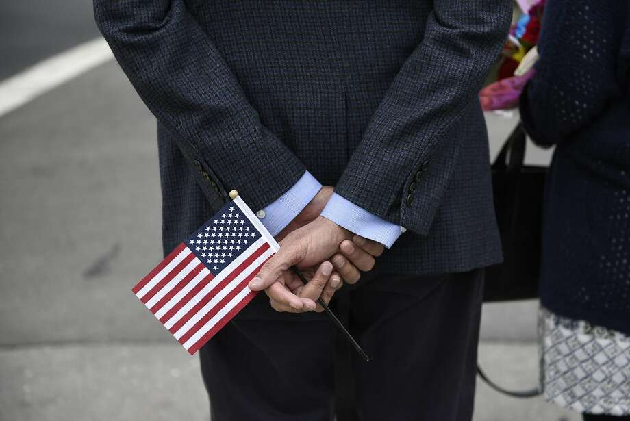 New U.S. citizen Farook Desai, from India, holds an American flag following a U.S. citizenship naturalization ceremony held at the Paramount Theater in Oakland on June 7. Photo: Michael Short, Special To The Chronicle