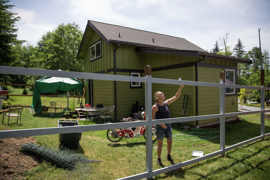 Barbara Brown paints the fence surrounding her new home in Vashon's new affordable housing development, The Sunflower, on Tuesday, June 6, 2017. Owners must earn 80 percent or less of King County's median income, but are free to upgrade the house as they see fit, as long as the footprint stays the same. Photo: GRANT HINDSLEY, SEATTLEPI.COM / SEATTLEPI.COM