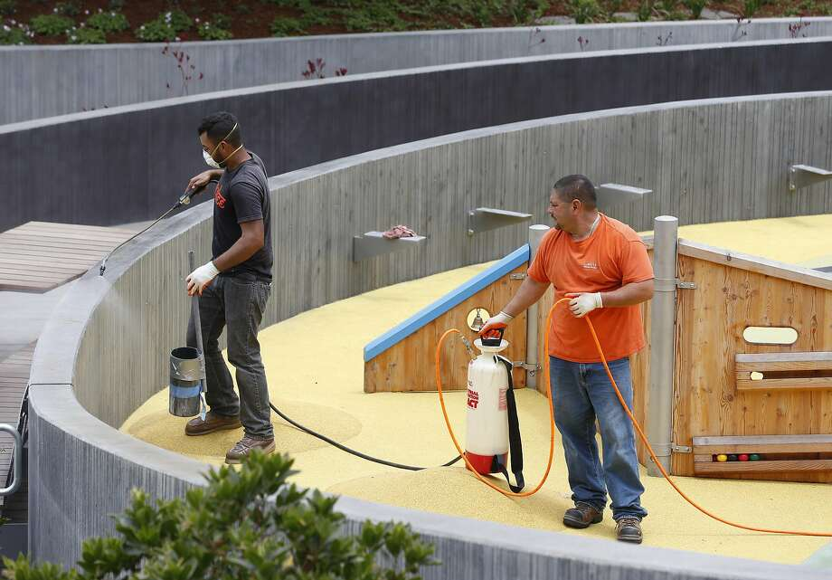 Alberto Maya (left) and Hector Acosta spray a weather sealant on concrete in preparing the playground. Photo: Paul Chinn, The Chronicle