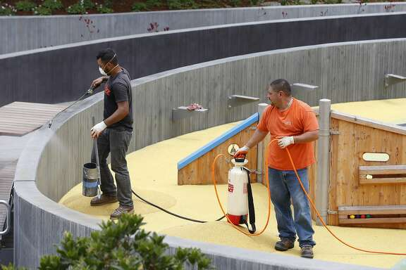 Alberto Maya (left) and Hector Acosta spray a weather sealant on concrete surfaces at the Mountain Lake Park playground in San Francisco, Calif. on Wednesday, June 7, 2017. The playground is set to reopen after an extensive renovation.