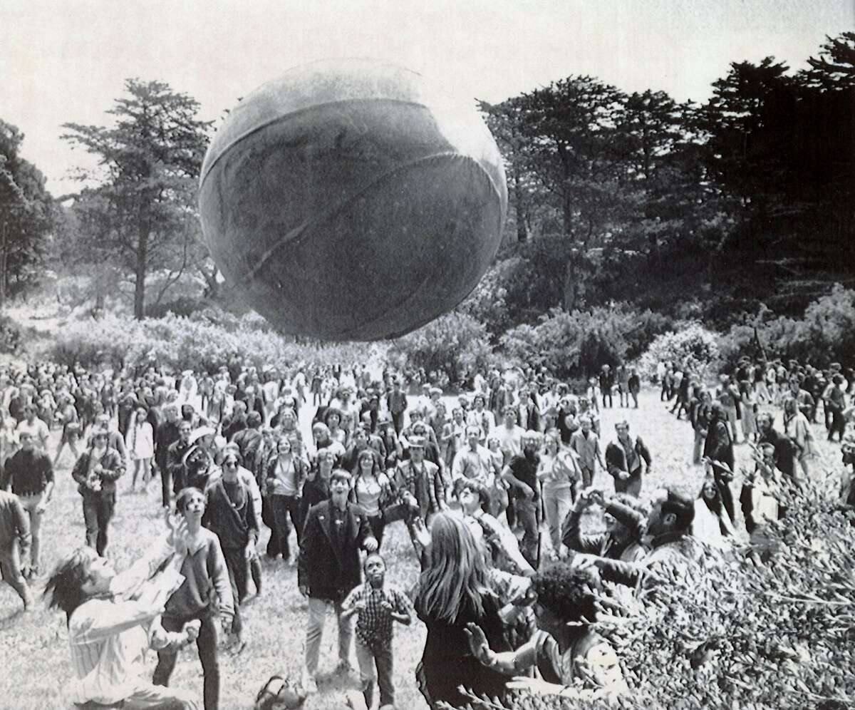 """June 21, 1967 - Crowds of hippies gather in Golden Gate Park during the """"Summer of Love"""" to welcome the first day of that season. A huge inflated ball, painted to represent a globe, is kept aloft by the celebrants."""