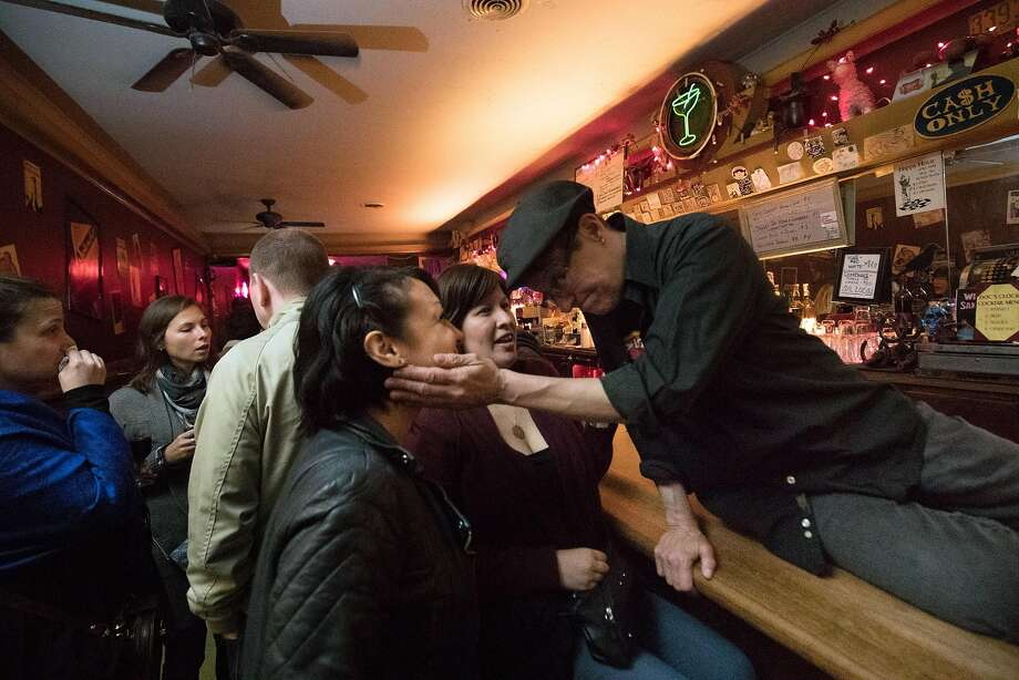 Doc's Clock bartender Lisa Francis (right) shares an affectionate moment with Tricia Green (left) and Marthaluz Quiteno. Photo: Paul Kuroda, Special To The Chronicle