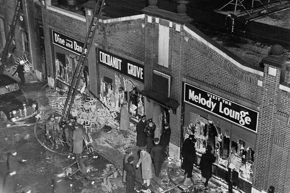 Police, firemen, reporters, and the curious gather at the entrance to the Cocoanut Grove nightclub in Boston on November 29, 1942. A fire on the previous evening incinerated the interior of the building, killing 492 and injuring 270, but leaving little apparent exterior damage. The high loss of life was due mainly to a lack of exits and the rapid growth of the blaze.