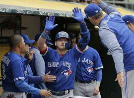Toronto Blue Jays' Josh Donaldson, center, is congratulated after hitting a two-run home run against the Oakland Athletics during the tenth inning of a baseball game in Oakland, Calif., Wednesday, June 7, 2017. (AP Photo/Jeff Chiu)