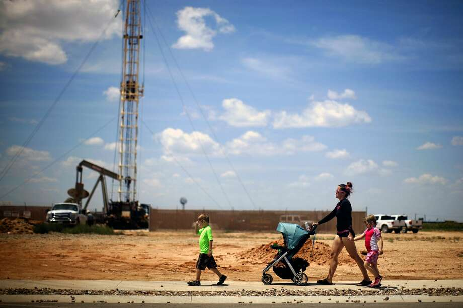 A woman walks with children past an active oil and gas exploration site after leaving the community pool in the D.R. Horton Legacy home community in Midland. The subdivision is located very close to several oil and gas locations. James Durbin/Reporter-Telegram Photo: James Durbin