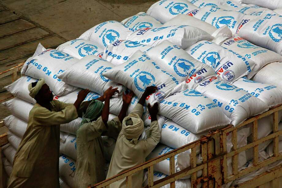 Sudanese workers in May offload U.S. aid destined for South Sudan from the World Food Programme (WFP) at Port Sudan. (Ashraf Shazly/AFP/Getty Images) Photo: ASHRAF SHAZLY, Stringer / AFP or licensors