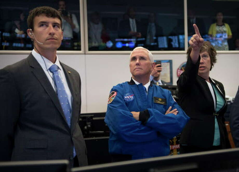 Vice President Mike Pence, center, listens to NASA Deputy Chief Flight Director Holly Ridings, right, and NASA Flight Director Rick Henfling during a tour of the Christopher C. Kraft Jr. Mission Control Center in Houston on Wednesday, June 7, 2017. NASA chose 12 new astronauts Wednesday from its biggest pool of applicants ever, selecting seven men and five women who could one day fly aboard the nation's next generation of spacecraft. (Michael Ciaglo/Houston Chronicle via AP) Photo: Michael Ciaglo, Associated Press / Michael Ciaglo