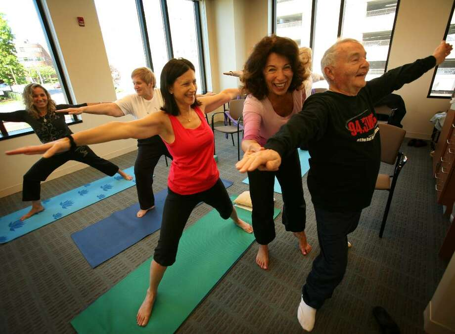 Yoga instructor Susan Kiley of Trumbull works with students from left; Siuzi Renzulli of Bridgeport, Vanessa Marshall of Trumbull, Sharon O'Connell of Fairfield, and Bernardo Vittori of Trumbull at the CT Challenge Integrative Survivorship Center at St. Vincent's Hospital in Bridgeport. Photo: Brian A. Pounds / Connecticut Post