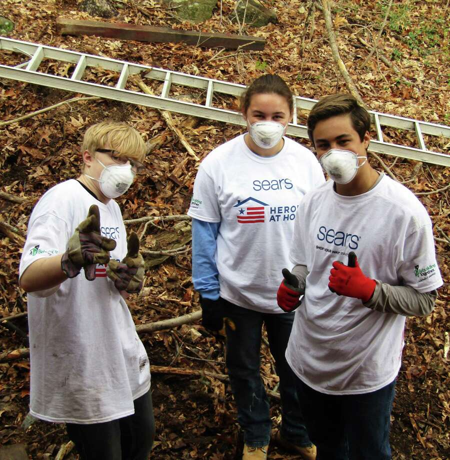 Volunteers, from left to right, Dan Lane, Rebecca Riter and Paul Riter, members of the New Fairfield Congregational Church Youth Group, take a break from their outdoor cleanup task at a home in Sherman during Rebuilding Together Litchfield County's recent Rebuild Day. Photo: Courtesy Of Rebuilding Together Litchfield County / The News-Times Contributed