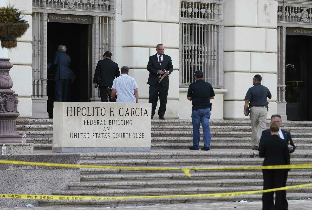 Individuals head back into the Hipolito Garcia Federal Building and U.S. Courthouse after bomb experts detonated a suspicious package Wednesday.
