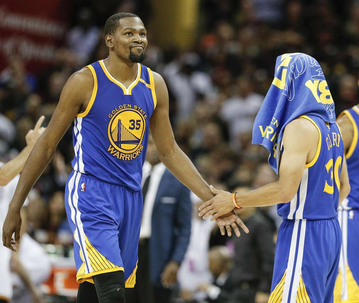 Golden State Warriors' Kevin Durant and Stephen Curry slap hands in the fourth quarter during Game 3 of the 2017 NBA Finals at Quicken Loans Arena on Wednesday, June 7, 2017 in Cleveland, Ohio