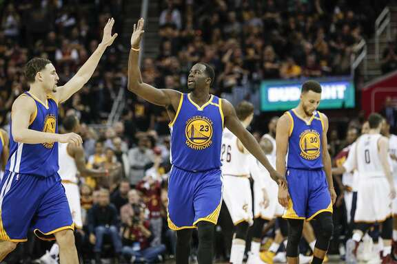 Golden State Warriors' Klay Thompson and Draymond Green high five in the fourth quarter during Game 3 of the 2017 NBA Finals at Quicken Loans Arena on Wednesday, June 7, 2017 in Cleveland, Ohio