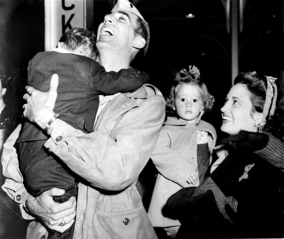 "Returning serviceman Lt. Earl Pizzo is greeted by his family at Houston's Southern Pacific Station, October 1945. Titled ""Daddy, Daddy, Daddy"" the picture shows 3-year-old Thomas Earl Pizzo Jr., in his father's arms, and 2-year-old Winnie Jo, bewildered by the fuss, in the arms of her mother. Photo: Caroline Valenta, HP Staff / Houston Chronicle"