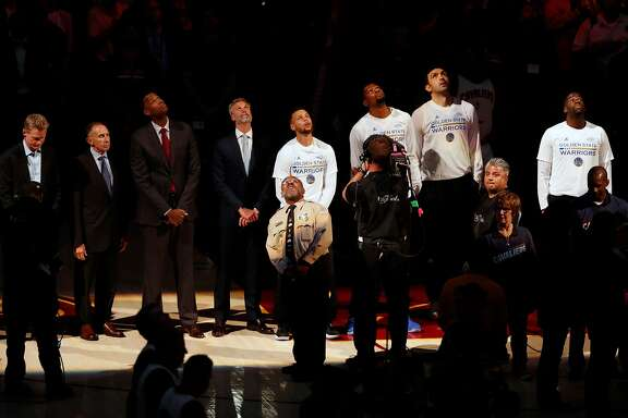 Golden State Warriors line up for National Anthem before Warriors' 118-113 win over Cleveland Cavaliers in Game 3 of the NBA Finals at Quicken Loans Arena in Cleveland, Ohio, on Wednesday, June 7, 2017.