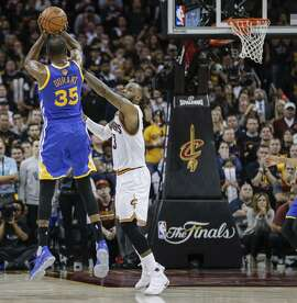 Warriors forward Kevin Durant shoots the game-winning three-pointer over the Cavaliers' LeBron James in the final minute.