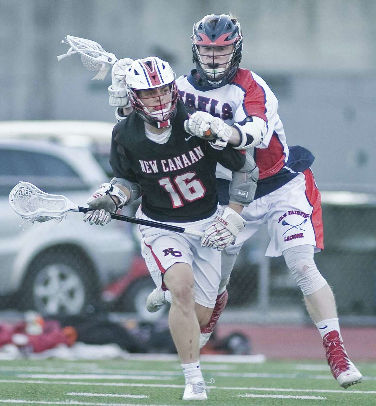 NEW CANAAN 21, NEW FAIRFIELD 6: New Canaan's Graham Braden takes a hit from New Fairfield's Colin Ford in the Class M boys lacrosse semifinal Wednesday at Brien McMahon High School in Norwalk