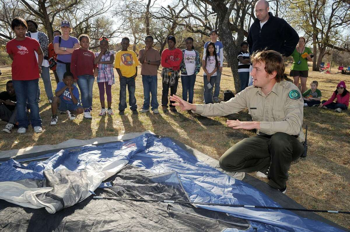 A Texas Outdoor Family guide instructs a group on how to put up a tent during a workshop at Enchanted Rock.