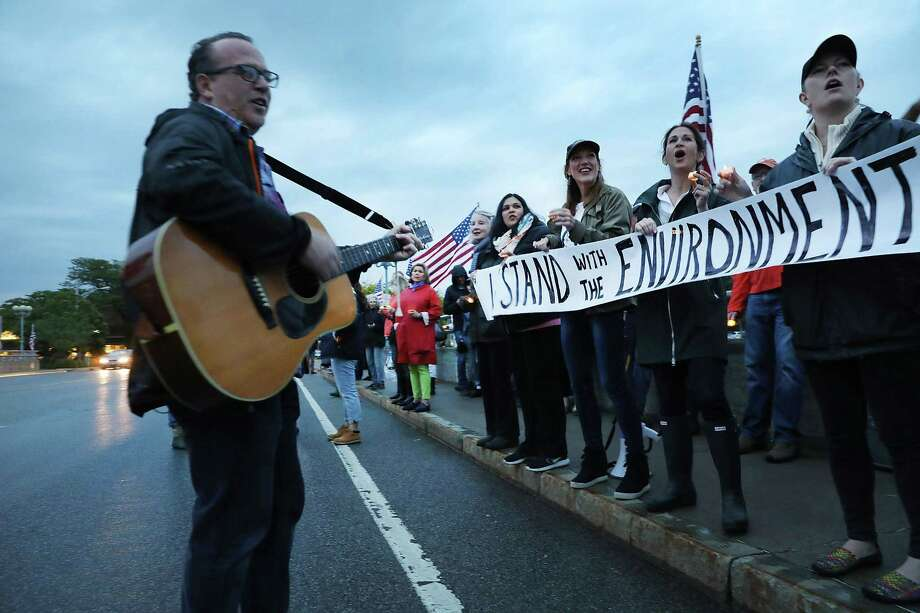 WESTPORT, CT - JUNE 04:  Dozens of Connecticut residents converge along a bridge at a vigil and rally for the environment and against President Donald Trump's recent decision to withdraw the United States from the Paris climate accord on June 4, 2017 in Westport, Connecticut. Close to 80 people attended the evening event where critics of the president's environmental policies held candles and sang songs. Trump's decision last week to pull out of the Paris climate agreement has outraged both world leaders and citizens alike.  (Photo by Spencer Platt/Getty Images) Photo: Spencer Platt / Getty Images / 2017 Getty Images