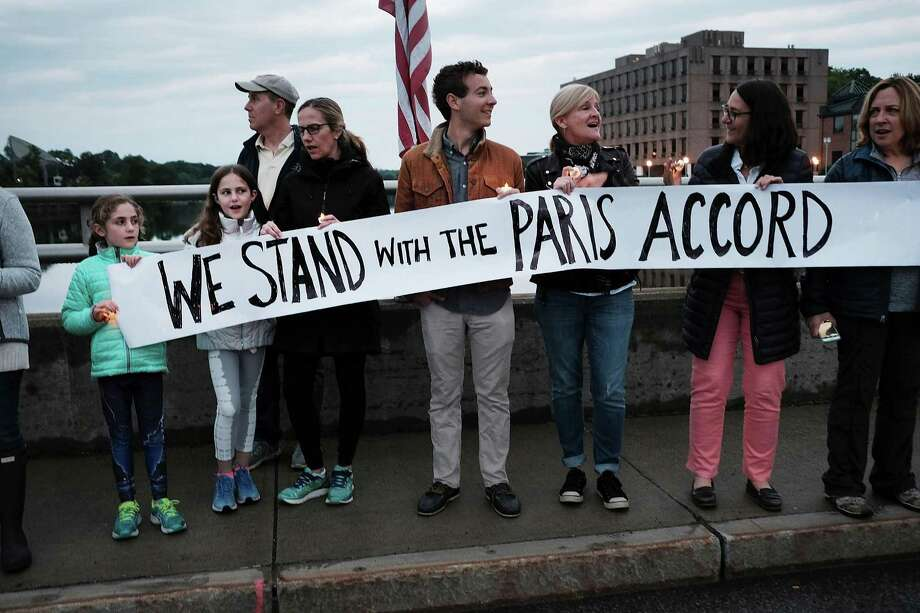 On Post Road Bridge, Westporters protest President Donald Trump's decision to withdraw the United States from the Paris climate accord at a June 4 vigil and rally. Photo: Spencer Platt / Getty Images / 2017 Getty Images