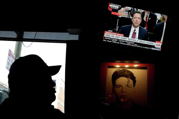 A patron at Ace's Bar watches a television broadcast of former FBI Director James Comey testify before the Senate Intelligence Committee on June 8, 2017 in San Francisco, California. People across the country are flocking to bars and restaurants to watch former FBI director as he testifies before the Senate Intelligence Committee about his conversations with U.S. President Donald Trump.