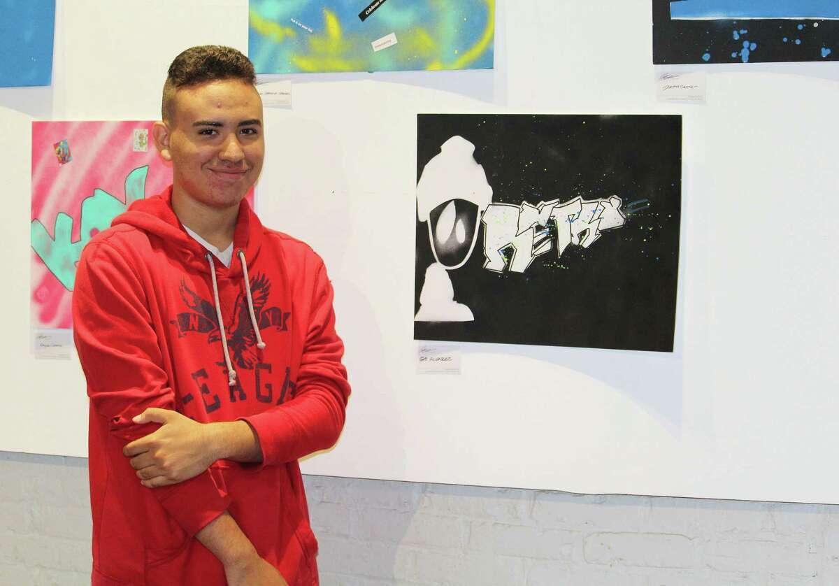 Gio Alvarez, 16, of Bridgeport, stands beside his artwork, on display at 305 Knowlton gallery in Bridgeport, Conn. on June 5, 2017.