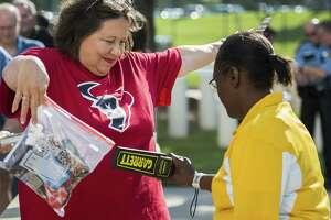 Houston Texans fan Regina Brower holds up a clear bag with her belongings as she goes through security screening at Reliant Stadium on Aug. 17, 2013, in Houston. The Alamodome is instituting a policy similar to one the National Football League has in place at stadiums.