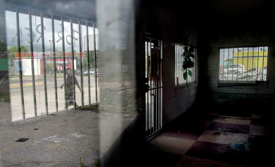 A man is seen through a window reflection as he walks by an empty building on Cullen Boulevard, in the Sunnyside neighborhood, Thursday, June 1, 2017, in Houston. The business that previously occupied the space moved across the street, and the building is now empty. Photo: Jon Shapley, Houston Chronicle / © 2017 Houston Chronicle