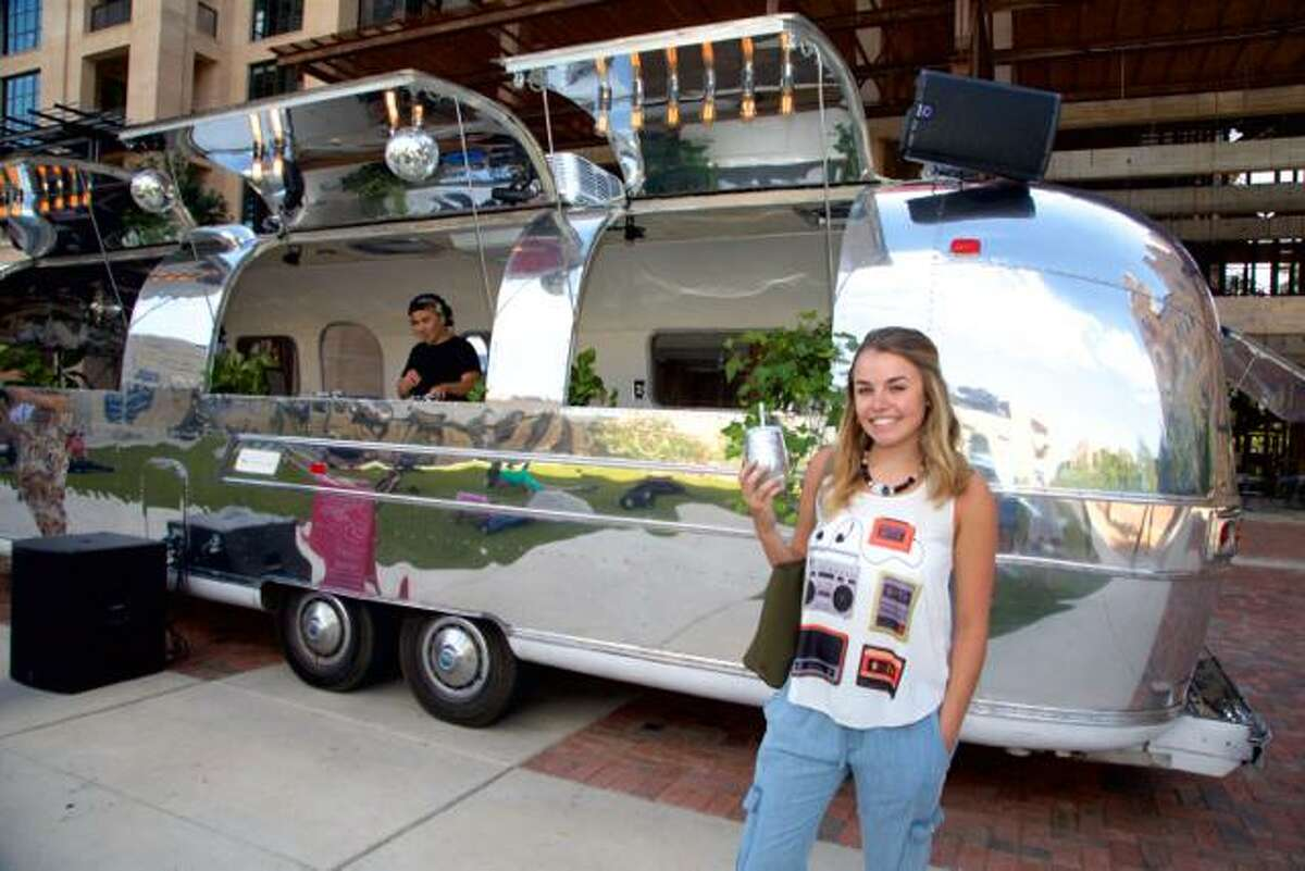 Delaney Dryden is shows off her shiny silver drink in front of the shiny silver Sound Cream Airstream.