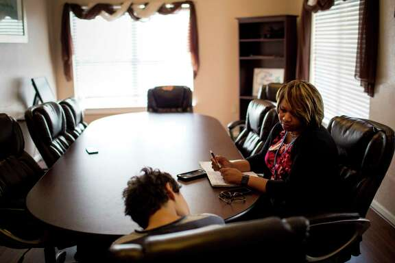 Shitonda Johnson, right, an investigator with CPS, talks to a 13-year-old boy after he was returned to his residential treatment facility, Thursday, May 4, 2017, in Baytown. The boy, who has been diagnosed with multiple mental disorders, said he had slept in an abandoned house with some friends.