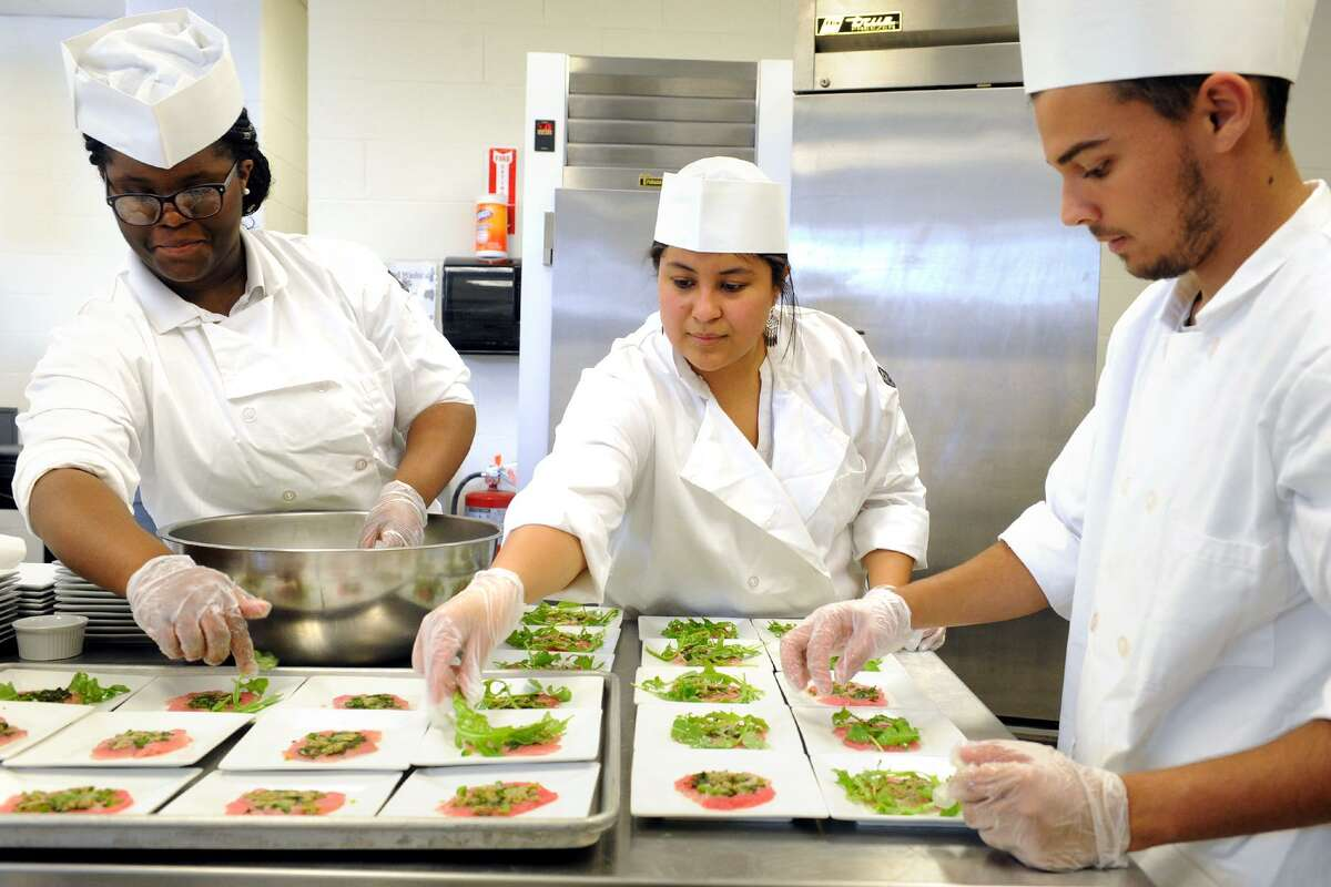 From left, Breanna Shand, Nayelli Cuevas and David Torres, Aqua Chefs at the Bridgeport Regional Aquaculture School, help prepare servings of Tuna Carpaccio during the Culinary Culture program in Bridgeport, Conn. June 7, 2017.
