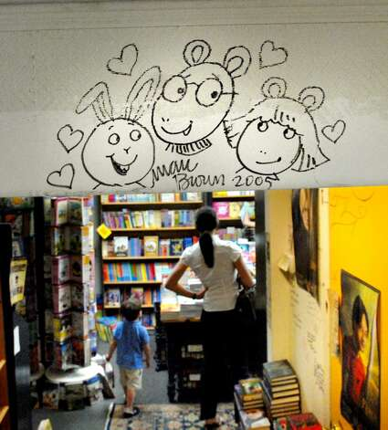 "Drawings and signatures of successful writers can be seen all over the walls at Diane's Books of Greenwich on Grigg Street.  Here is a drawing from 2005 of the main characters from ""Arthur,"" Buster, D.W. and Arthur and the signature of their creator Marc Brown as seen on Tuesday, June 8, 2010.  Diane's is celebrating 20 years in the book business. Photo: Bob Luckey / Greenwich Time"