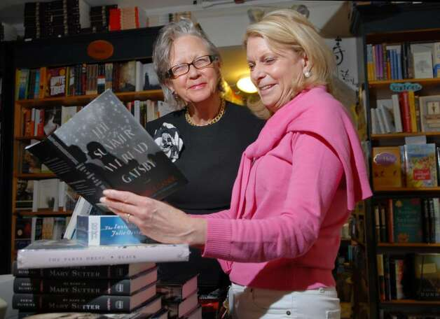 "Diane Garrett owner of Diane's Books of Greenwich, left, shows the book, ""The Summer We Read Gatsby"" by Danielle Ganek, to customer and friend, Laurie Atcheson of Greenwich, inside Garrett's Greenwich store, Tuesday, June 8, 2010.  Diane's is celebrating 20 years in the book business. Photo: Bob Luckey / Greenwich Time"