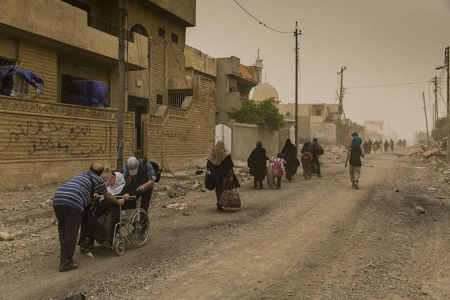 People leave the besieged city of Mosul, Iraq, amid a sandstorm last month. The United Nations accuses Islamic State militants of slaughtering civilians. Photo: IVOR PRICKETT, NYT