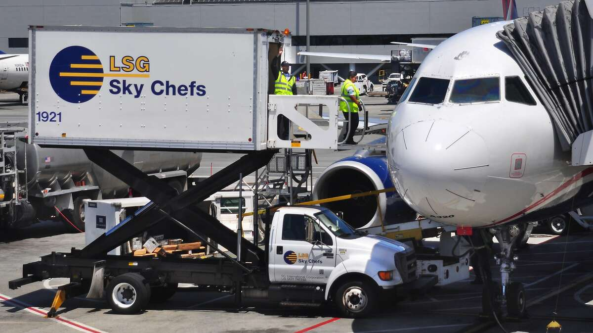 Workers for LSG Sky Chefs service a commercial airliner parked at the gate at San Francisco International Airport. Many workers are being reassigned to the San Jose airport.