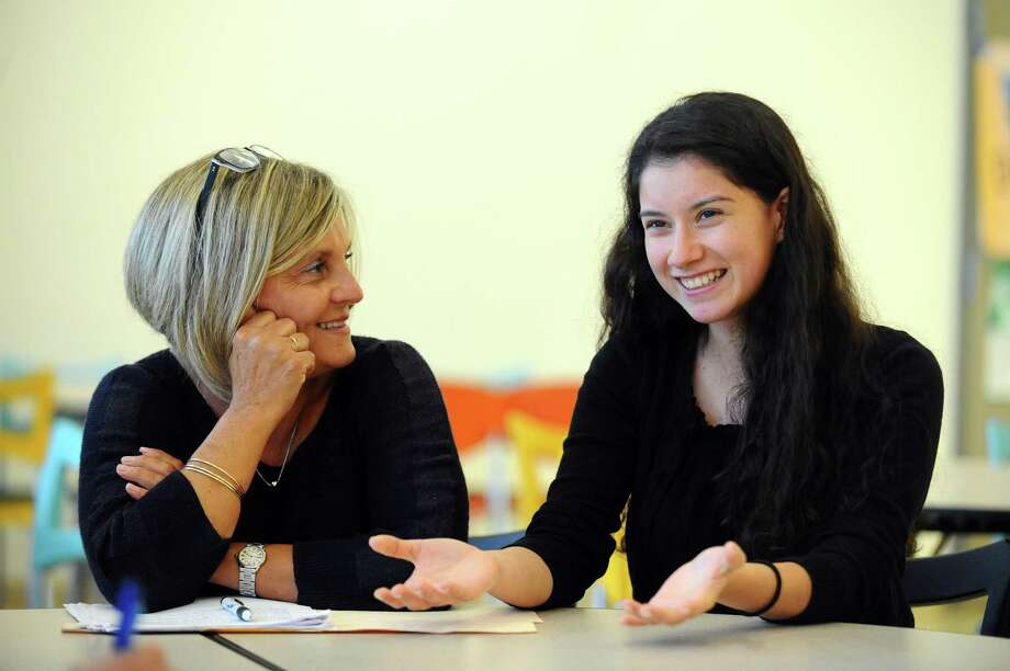 Beverly Reyes, 18, right, and her Starfish Connection mentor, Maria Millan, share one of their stories from the program. Photo: Michael Cummo / Hearst Connecticut Media / Stamford Advocate