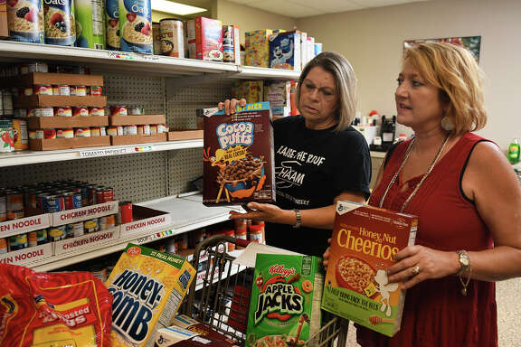 Humble Area Assistance Ministries (HAAM) Food Pantry volunteer Maria Rodriguez, left, and HAAM Executive Director Millie Garrison fill an order in the pantry on June 7, 2017. (Photo by Jerry Baker/Freelance)