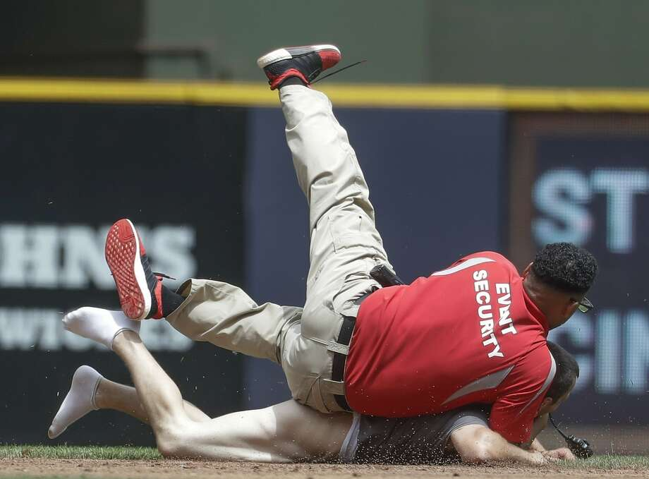 A security guard tackles a fan that ran on the field during the second inning of a baseball game between the Milwaukee Brewers and the San Francisco Giants Thursday, June 8, 2017, in Milwaukee. (AP Photo/Morry Gash) Photo: Morry Gash, Associated Press