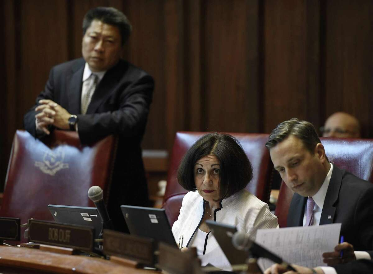 State Sen.Toni Boucher, R- Wilton, looks up as colleagues Sen. Tony Hwang, R-Fairfield, and State Sen. Majority Leader Bob Duff, D-Norwalk, listen on the final day of session at the State Capitol, Wednesday, June 7, 2017, in Hartford, Conn.