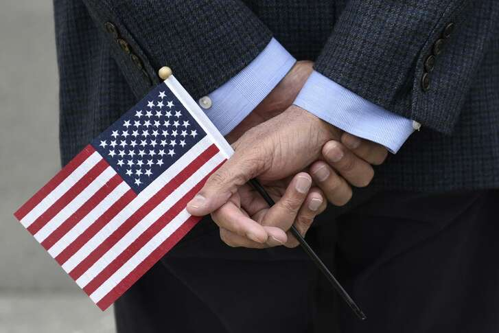 New U.S. citizen Farook Desai, from India, holds an American flag following a U.S. citizenship naturalization ceremony held at the Paramount Theater in Oakland, CA, on Wednesday June 7, 2017.