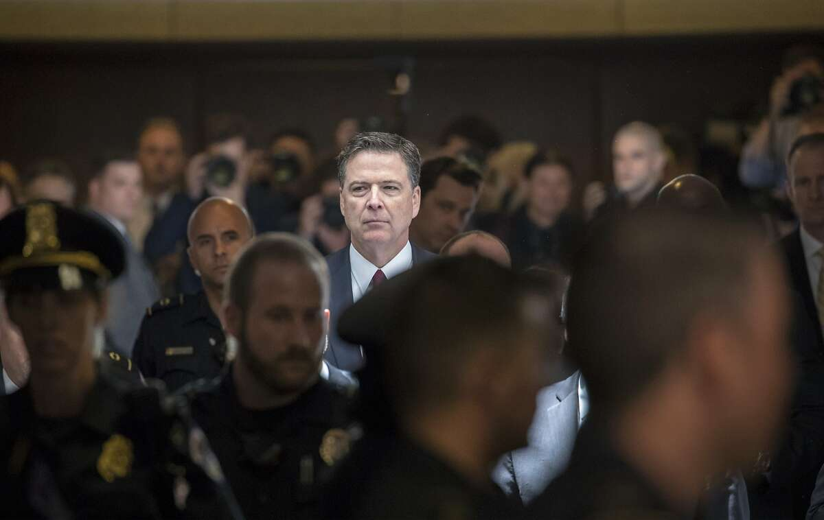 """Former FBI director James Comey walks through a corridor on the way to a secure room to continue his testimony to the Senate Select Committee on Intelligence, on Capitol Hill in Washington, Thursday, June 8, 2017. Comey, who was fired by President Donald Trump, told the panel in open session that Trump repeatedly pressed him for his """"loyalty"""" and directly pushed him to """"lift the cloud"""" of investigation by declaring publicly the president was not the target of the probe into his campaign's Russia ties. (AP Photo/J. Scott Applewhite)"""