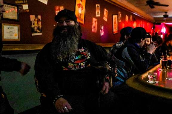 Security guard Mike Burt laughs as a customer enters Doc's Clock bar in San Francisco, California, on Tuesday, May 23, 2017.